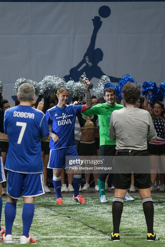 Guti lifts a trophy next to Iker Casillas during 'Partido X La Ilusion' by Iker Casillas Foundation at Palacio de los Deportes on December 23, 2012 in Madrid, Spain.