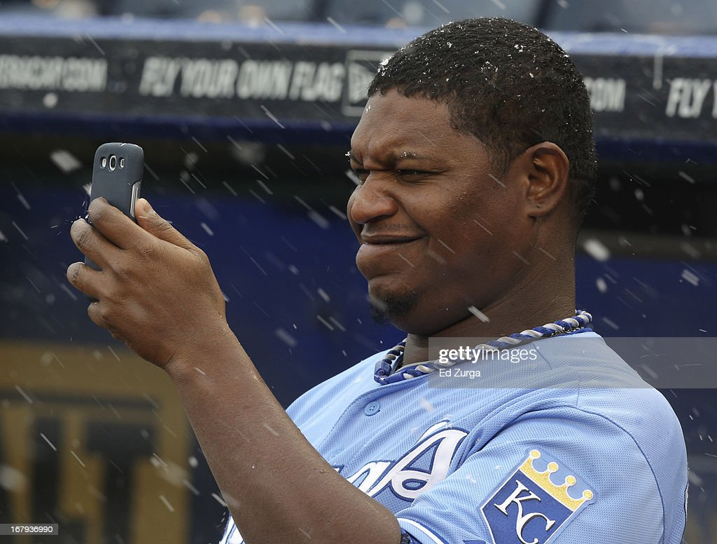 J.C. Gutierrez #27 of the Kansas City Royals takes a photo of snow falling during a delay in a game against the Tampa Bay Rays at Kauffman Stadium on May 2, 2013 in Kansas City, Missouri. The game was postponed due to the weather.
