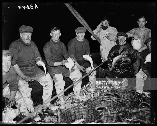 Gutting fish c 1930 A photograph of a group of fishermen gutting their catch on the decks of a trawler taken by an unknown photographer for the Daily...