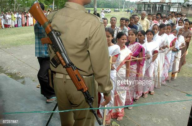 Local residents guarded by security personell stand in a queue as they wait to vote in the state assembly elections in Guwahati 03 April 2006 Voting...