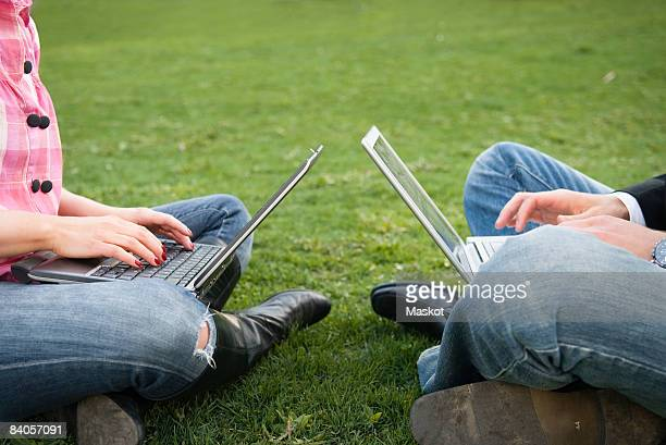 Guy and girl opposite to each other with computers