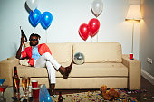 African man with bottle of champgne sitting on sofa at party