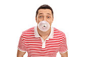 Young guy blowing up a bubble from a chewing gum isolated on white background