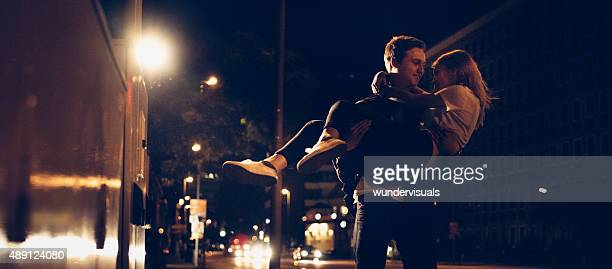 Guy carrying his girlfriend on an urban street at night