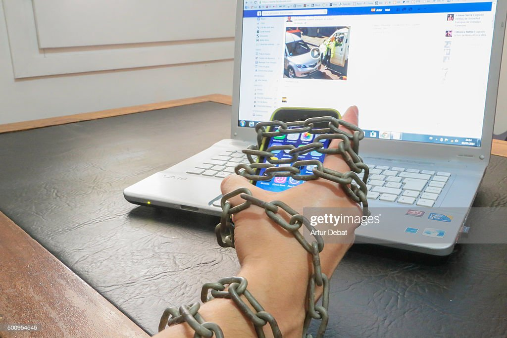 Guy chained to smartphone and internet laptop Conceptual picture for internet addiction