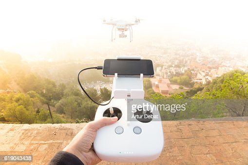 Guy controlling a drone from personal perspective holding remote controller and flying the drone from viewpoint hill with the city views on sunrise.