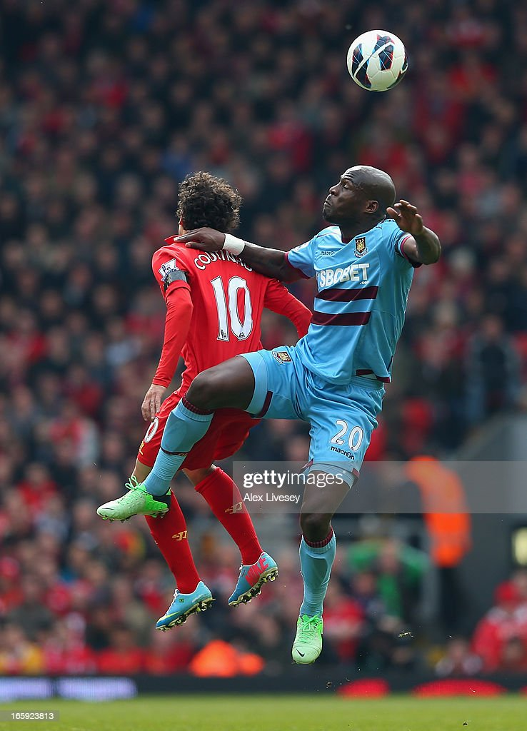 Guy Demel of West Ham United goes up for a header with Coutinho of Liverpool during the Barclays Premier League match between Liverpool and West Ham United at Anfield on April 7, 2013 in Liverpool, England.