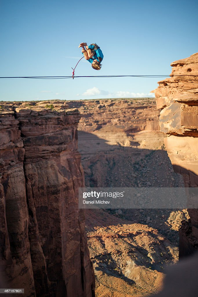 Guy doing a flip on a slack line, over a canyon.