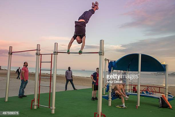 Guy doing bar spins on Crossfit routine in a open outside gym in the shoreline at sunset