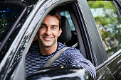 Guy in car driving, smiling