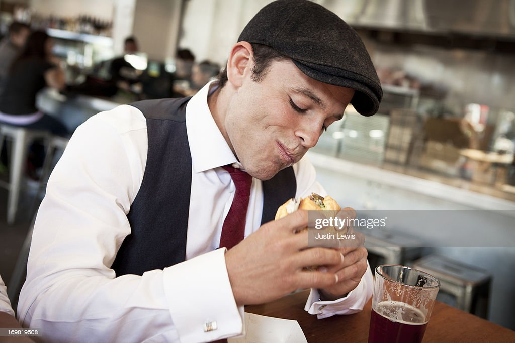Guy eats a sandwhich in urban restaurant : Stock Photo
