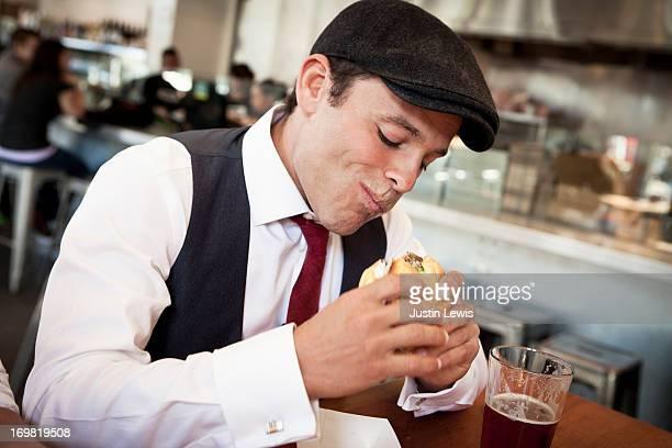 Guy eats a sandwhich in urban restaurant