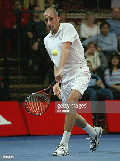 Guy Forget of France returns in the finals match against John McEnroe of USA during the Honda Challenge 2003 at The Royal Albert Hall on December 7...