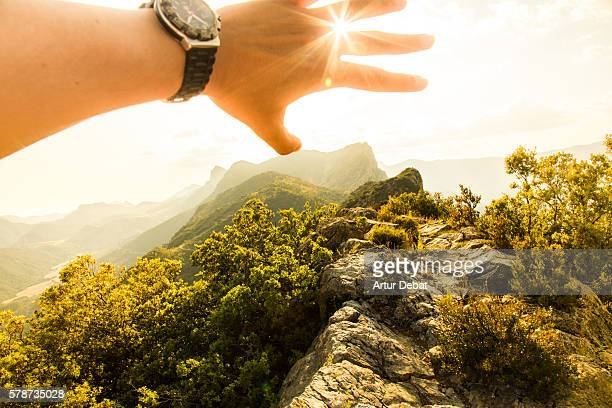 Guy from personal perspective covering from light with hand on top of summit surrounded by stunning mountains in the Catalan Pyrenees on sunset.