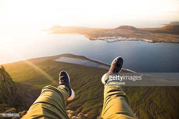 Guy from personal perspective flying his legs over the cliff in the volcanic island of Lanzarote from nice viewpoint during the sunset light with volcanic islands during a travel vacations through the island.