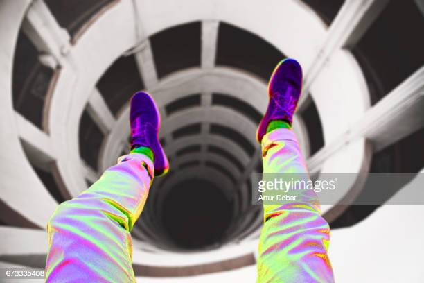 Guy from personal perspective taking a picture with legs over of a beautiful spiral geometric shape created by a parking ramp in a decay architecture building with nice vanishing point and vertigo feeling.