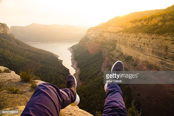 Guy from personal perspective with levitating legs flying over the stunning autumn landscape with cliffs and reservoir in the mountains of the Catalonia region.