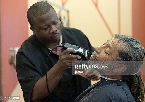 A man getting a shave in a barber shop