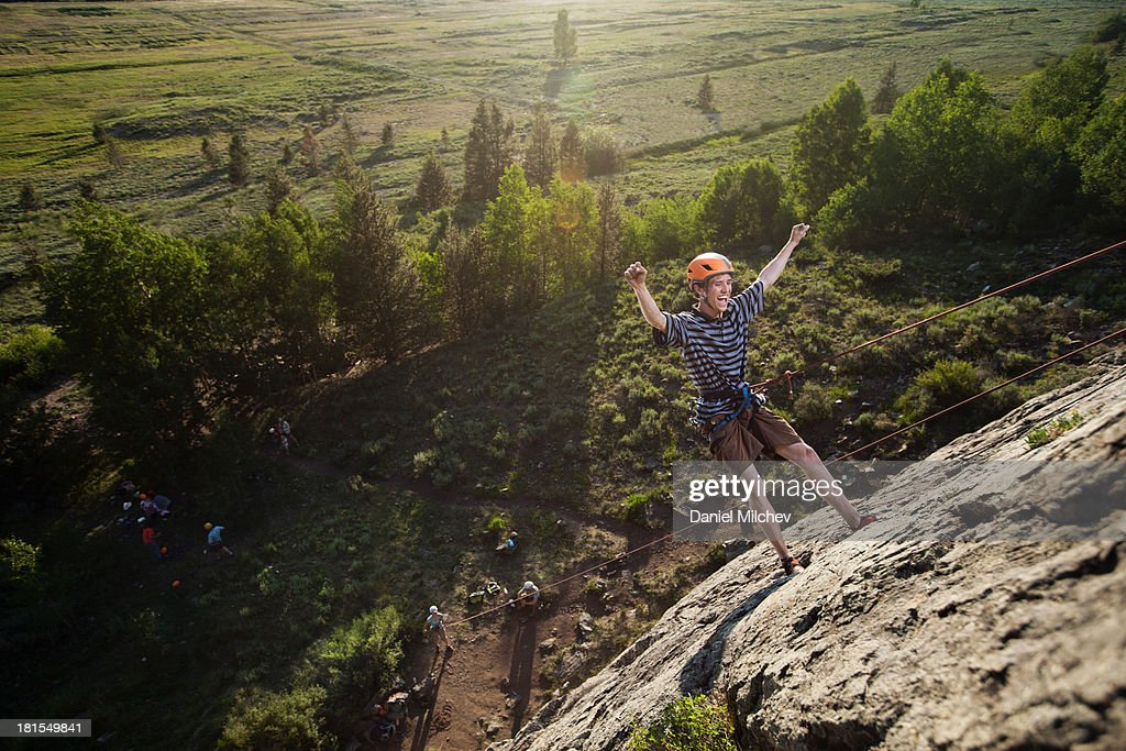 Guy having fun, after climbing a wall. : Stock Photo