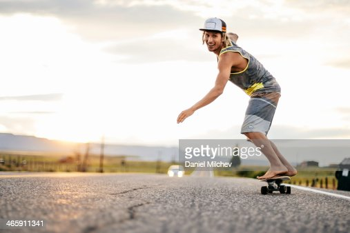Guy having fun with a skateboard at sunset.