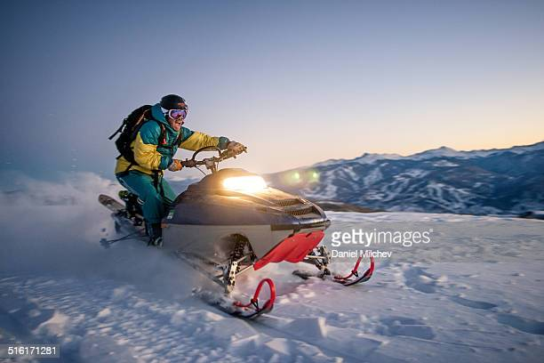 Guy having fun with a snowmobile in backcountry.