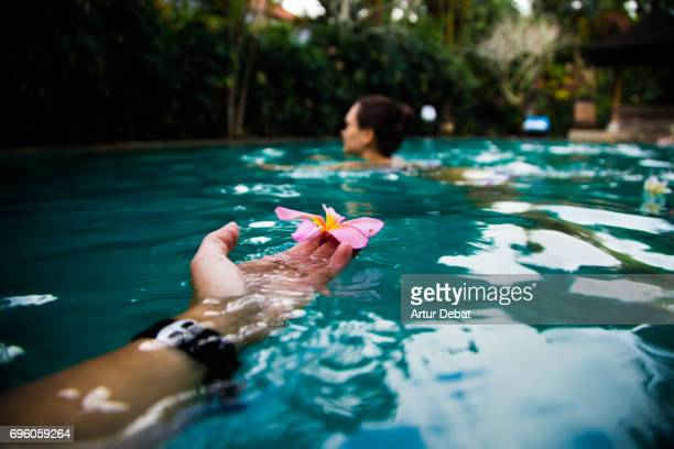 Guy holding from personal perspective a beautiful flower while swimming with girl in the Bali island during travel vacations in Indonesia.