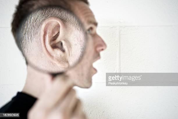 Garçon détient une loupe à oreille