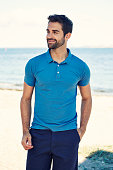 Guy in blue polo shirt on beach, smiling
