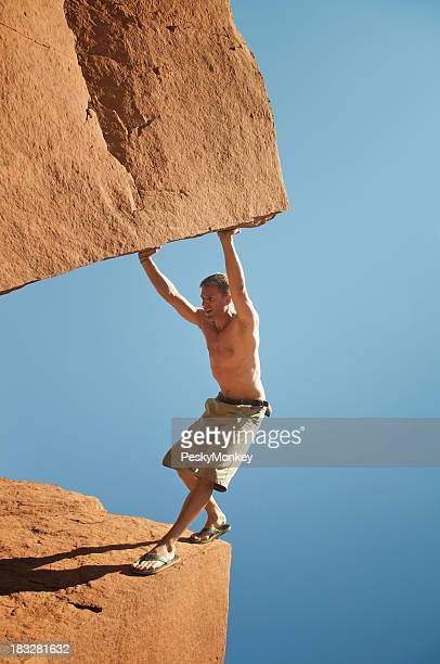 Guy in Shorts Stands Wedged Between Massive Boulders