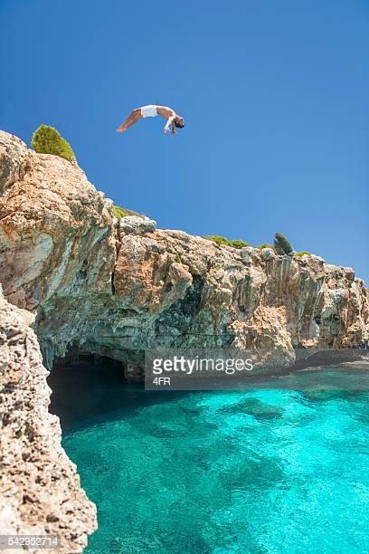 Mann springen auf einer Klippe ins Meer, Mallorca, Spanien