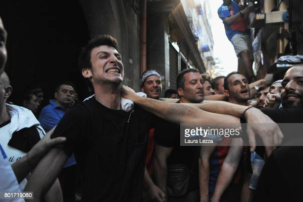 A guy kokes while men carry a 25metre tall wood and papiermache statue called 'giglio' during the annual Festa dei Gigli on June 26 2017 in Nola...