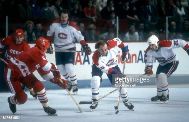 Guy Lafleur of the Montreal Canadiens skates on the ice with the puck as he is defended by Viacheslav Fetisov of the Soviet Union during an...