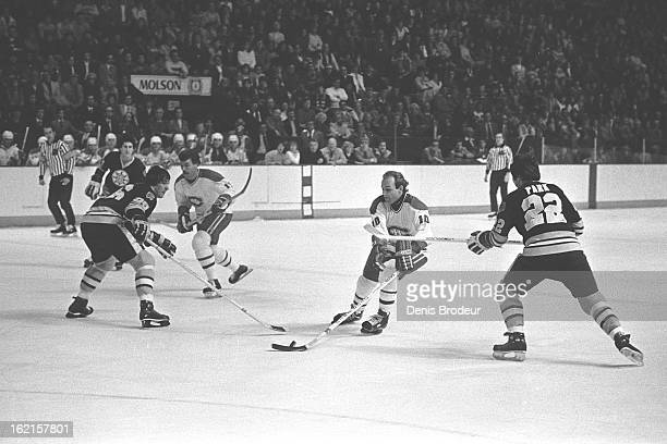 Guy Lafleur of the Montreal Canadiens skates with puck against Mike Milbury and Brad Park of the Boston Bruins during a game at the Montreal Forum...