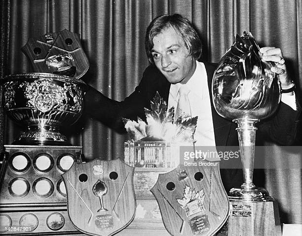 Guy Lafleur of the Montreal Canadiens stands next to the Art Ross Trophy Hart memorial Trophy Conn Smythe Trophy and the Lester B Pearson Trophy...