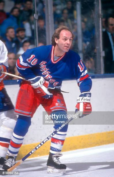 Guy Lafleur of the New York Rangers is hooked by an unidentified New York Islanders player during an NHL game on January 7 1989 at the Nassau...