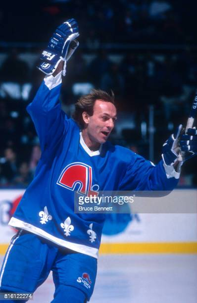 Guy Lafleur of the Quebec Nordiques skates on the ice as he celebrates a goal during an NHL game against the New York Islanders circa 1990 at the...