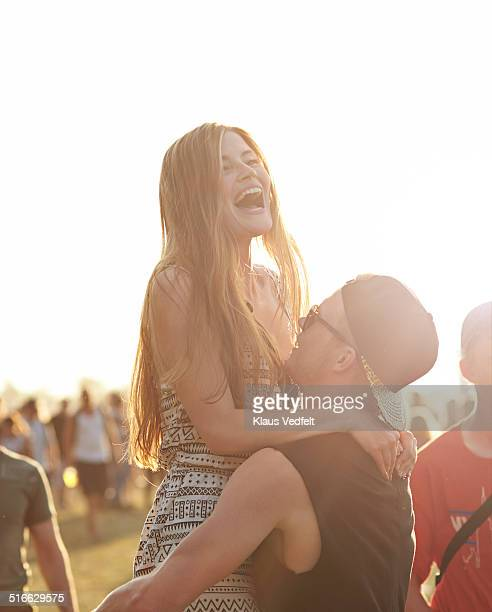 Guy lifting up girlfriend at outside festival
