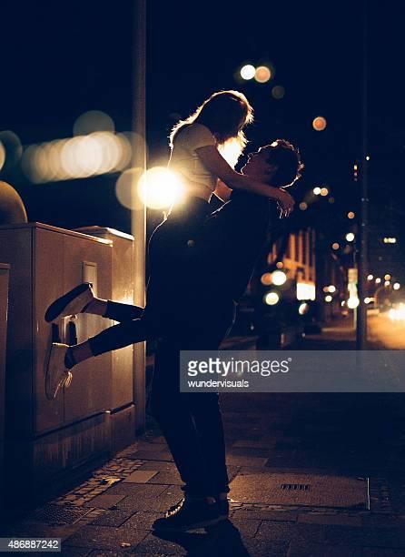 Mann heben Sie seine Freundin am späten Abend city street