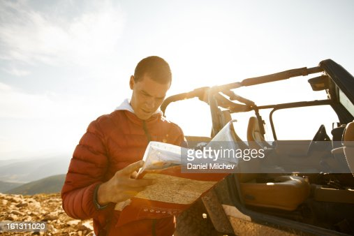 Guy looking at a map, next to a 4x4 vechicle. : Stock Photo