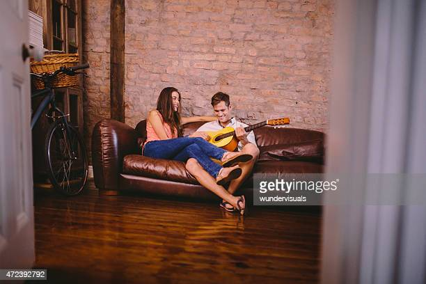 Guy playing guitar for his girlfriend on a couch