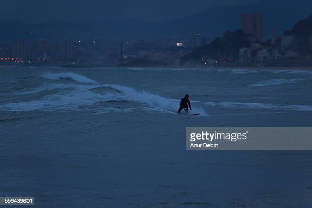 Guy practicing surf at dusk in the Barcelona's shoreline during the spring storms with the city lights on background Masnou Catalonia Europe