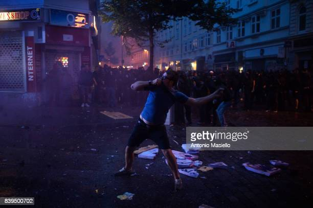 A guy pulls a stone against police during night of riots on July 7 2017 in Hamburg Germany German police and protesters clashed for three day during...