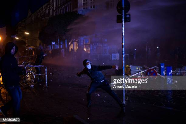 A guy pulls a stone against police during night of riots on July 8 2017 in Hamburg Germany German police and protesters clashed for three day during...