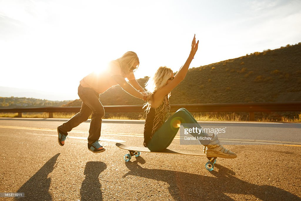 A guy pushing a girl on a skateboard. : Stock Photo