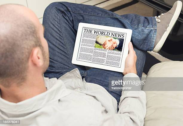 Guy reading a newspaper on digital tablet