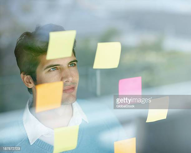 Guy reading reminders that are stuck on the glass
