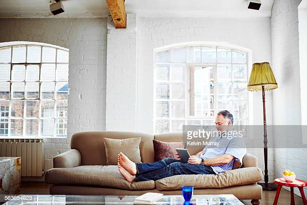 A guy relaxed on his sofa using a tablet