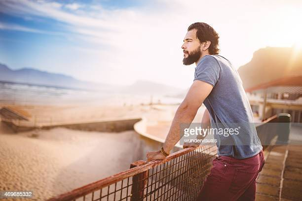 Guy relaxing looking at a beach in the evening