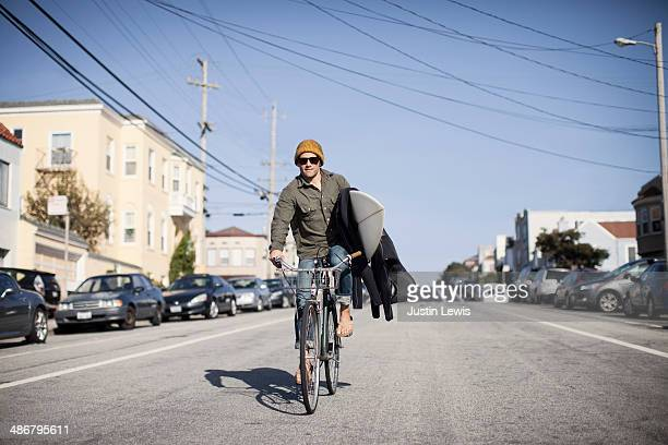 Guy riding a bike down street holding surfboard