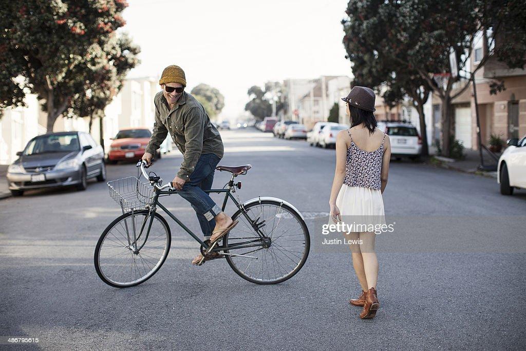 Guy riding circles around girl on bicycle